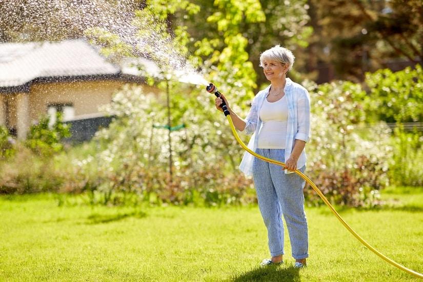 Frau sprengt ihren Rasen mit einem gelben Schlauch 138.