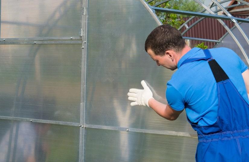 Heimwerker bringt die Wände eines Gewächshaus an