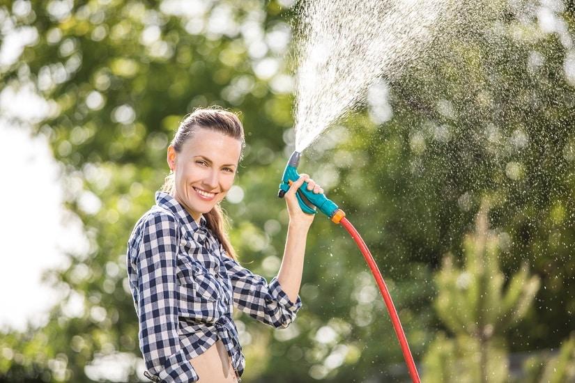Frau gießt mit einem Wand-Schlauchtrommel von Gardena