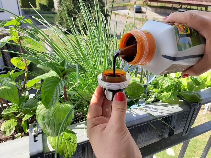 Gemüsedünger wird in Verschlusskappe abgemessen.
