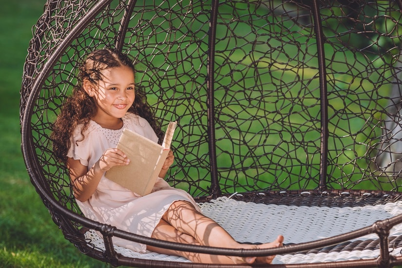 Ein Mädchen liest auf einer ausgefallenen Schwingliege