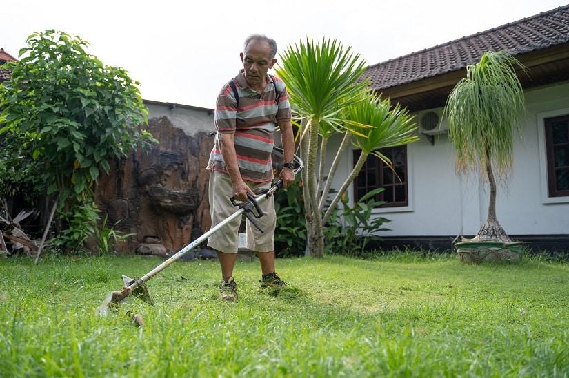 Hobbygärtner pflegt seinen Garten mit einer Elektrosense