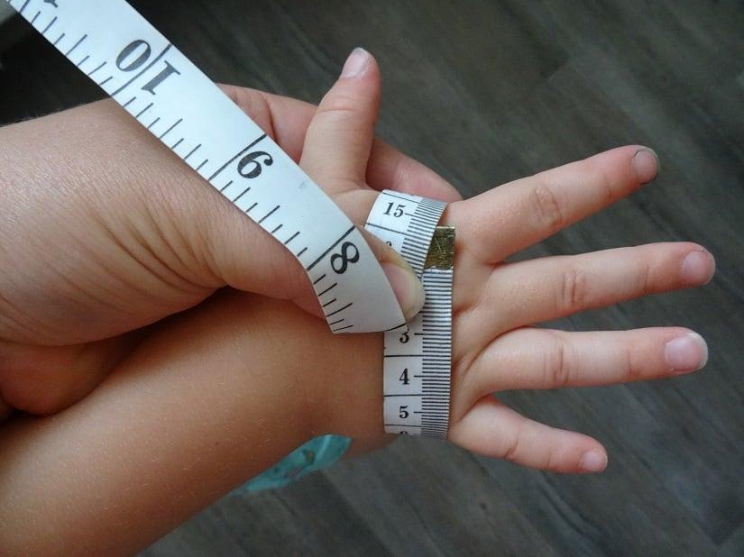 Zum Vermessen der Kinderhände das Maßband an der breitesten Stelle der Hand ohne Daumen umlegen.