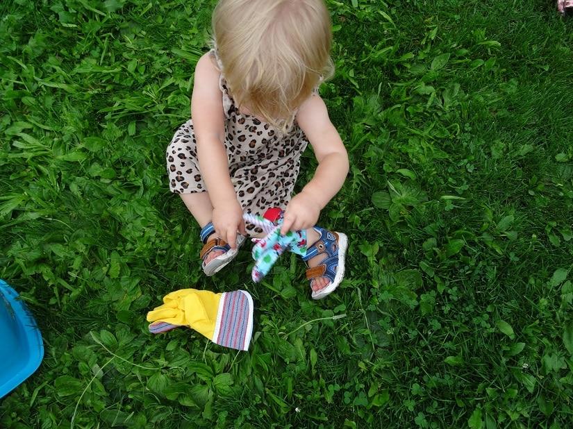 Bereits Kleinkinder wie unsere 1-Jährige zeigt Interesse an Gartenhandschuhe. Sie sind Teil des Natur-Spiels.