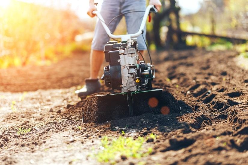 Gartenboden wird mit einem Gartenkultivator aufgelockert