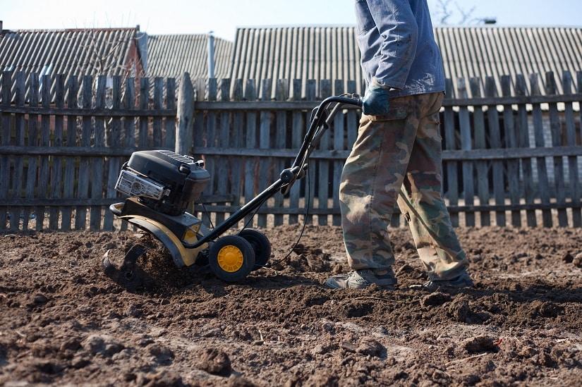mann bearbeitet den Boden mit einer Fräse
