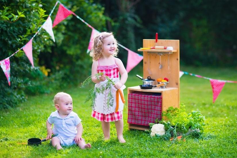 zwei kleine Kinder spielen mit einer Matschküche im Garten