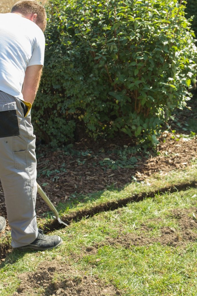 Mann legt eine Rasenmähkante an