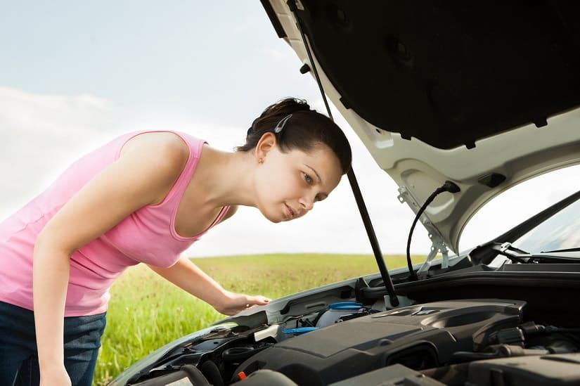 junge Frau schaut sich Schaden am Auto durch Marder an
