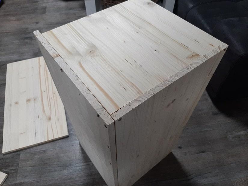 Schraube die Seitenteile von unten auf die Bodenplatte auf
